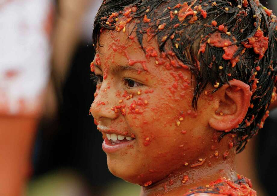 "A child covered with smashed tomato participates in the sixth annual tomato fight festival called ""tomatina"" in Sutamarchan, some 71 miles northeast of Bogota, Colombia, Sunday, June 10, 2012. Photo: Fernando Vergara, AP / AP"