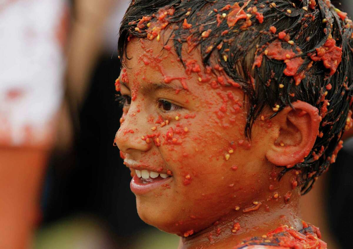 A child covered with smashed tomato participates in the sixth annual tomato fight festival called