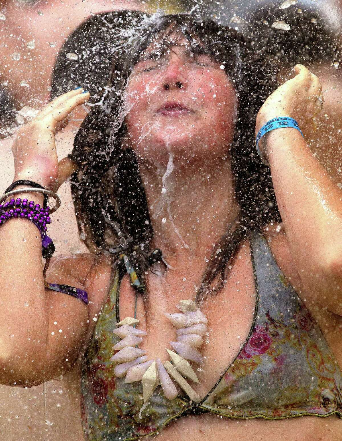 Lex Hirst, of Sydney,cools off in the Centeroo Fountain during the Bonnaroo Music and Arts Festival in Manchester, Tenn., Saturday, June 9, 2012.