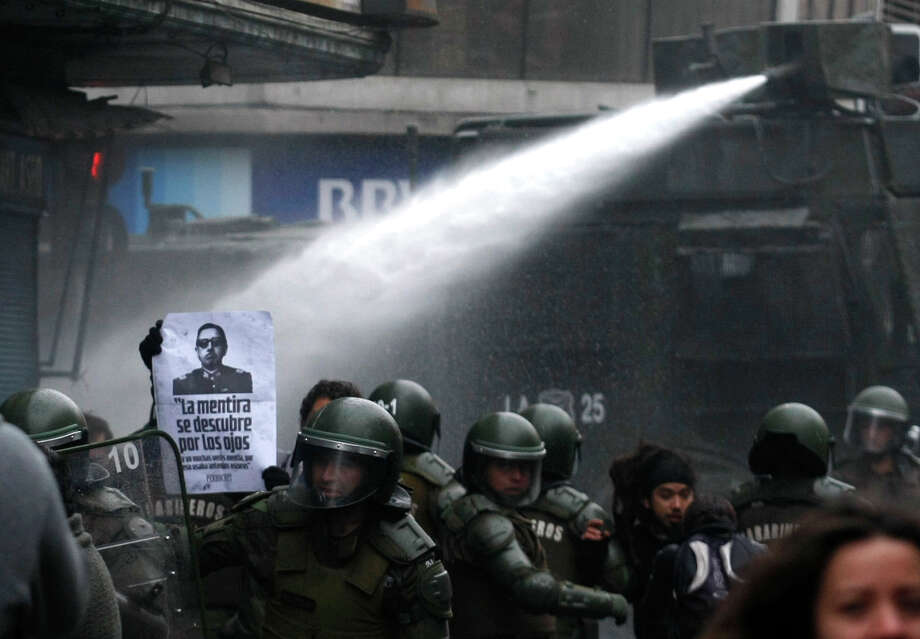 Riot police uses a water cannon to disperse a demonstration against the late Gen. Augusto Pinochet in Santiago, Chile, Sunday June 10, 2012.  Police used tear gas and water cannons to try to disperse hundreds of anti-Pinochet demonstrators protesting the premiere of a documentary, casting him as a national hero who saved Chile from communism, about the run-up to his dictatorship years. Photo: Luis Hidalgo, Associated Press / AP