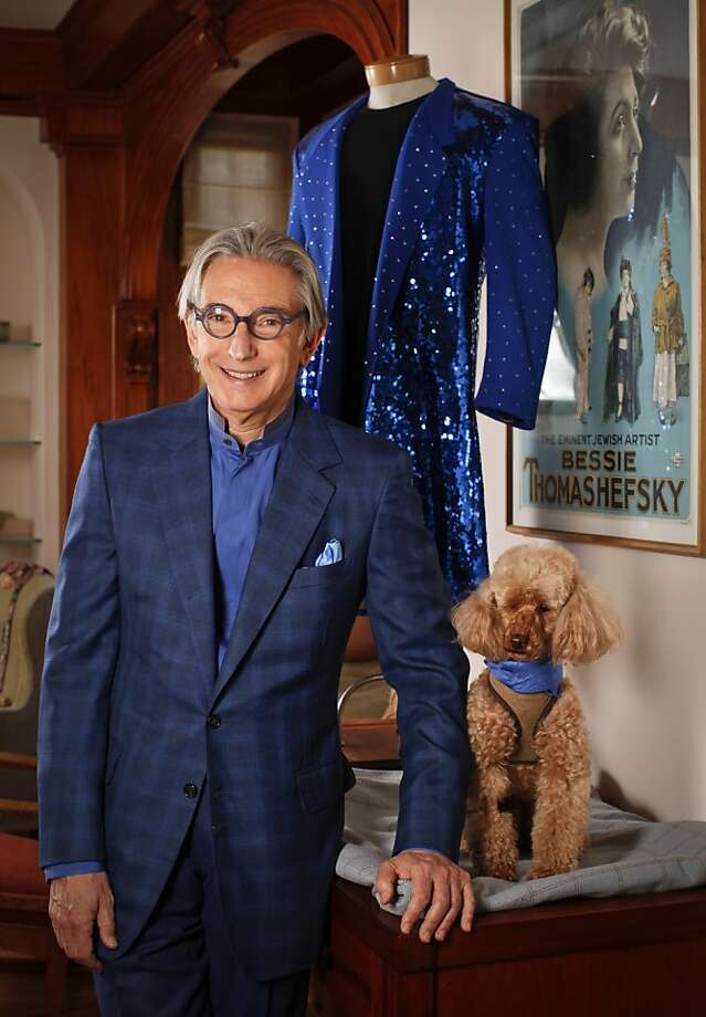 Michael Tilson Thomas, composer and music director of the San Francisco Symphony, is seen with his dog, Banda, and a suit worn by James Brown, rear, in his San Francsico, Calif., home on Friday, June 8, 2012.  The poster depicts his grandmother, Bessie Thomashefsky. Photo: Russell Yip, The Chronicle