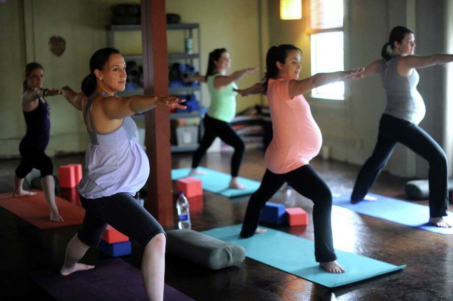 Becky Pitotti, left, and Lorien Whyte, center, assume the warrior pose with other women in a prenatal yoga class at Southtown Yoga Loft. Photo: Billy Calzada / San Antonio Express-News