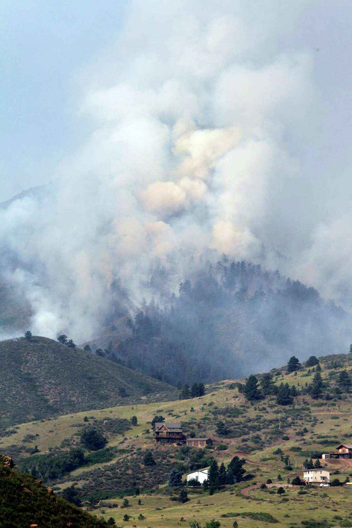 Fire burns on a hill with homes in the foreground on the High Park wildfire near Fort Collins, Colo., on Monday. The wildfire is burning out of control in northern Colorado, while an unchecked blaze choked a small community in southern New Mexico as authorities in both regions battled fires Monday.