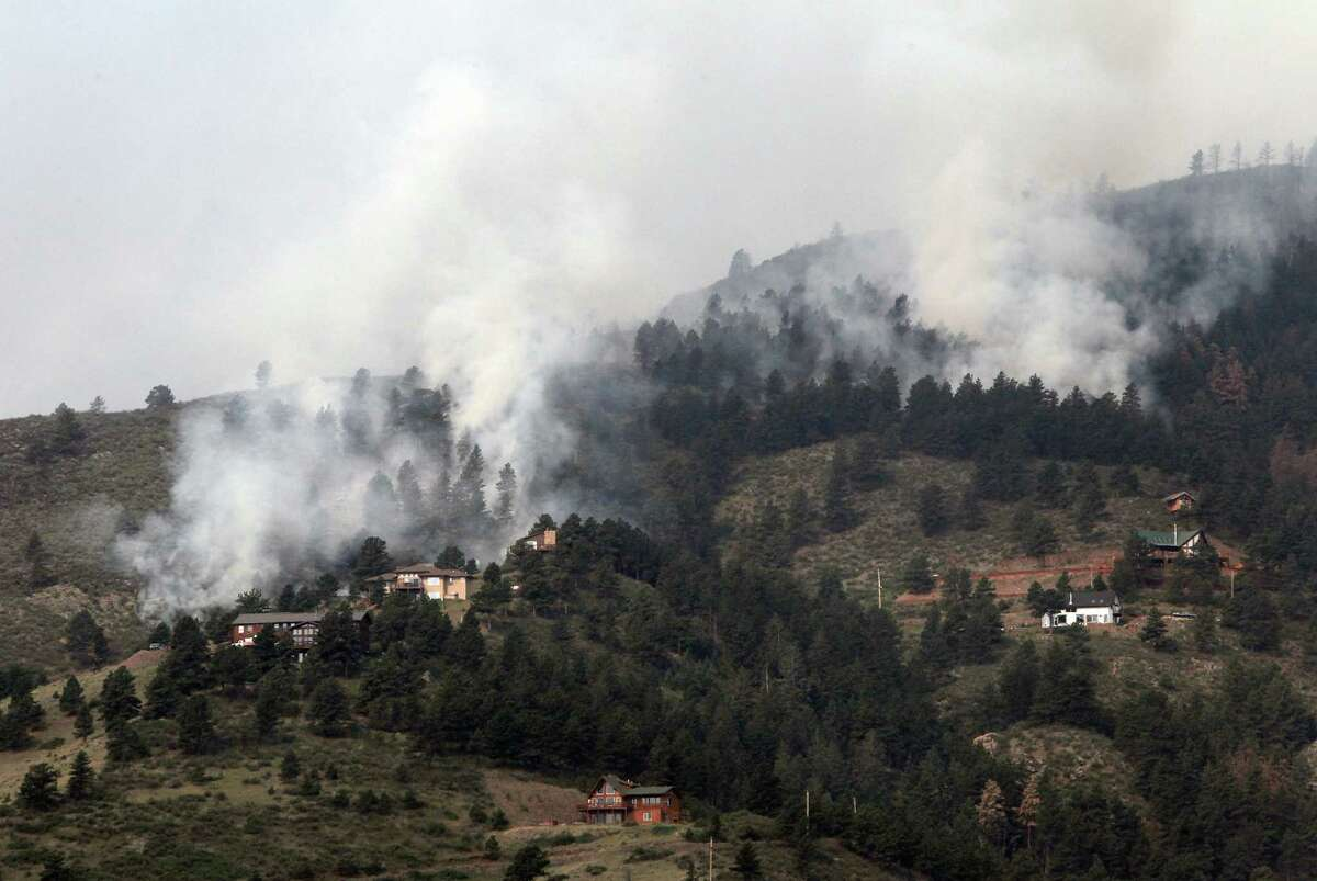 Fire burns in trees behind homes on the High Park wildfire near Fort Collins, Colo., on Monday. The wildfire is burning out of control in northern Colorado, while an unchecked blaze choked a small community in southern New Mexico as authorities in both regions battled fires Monday.