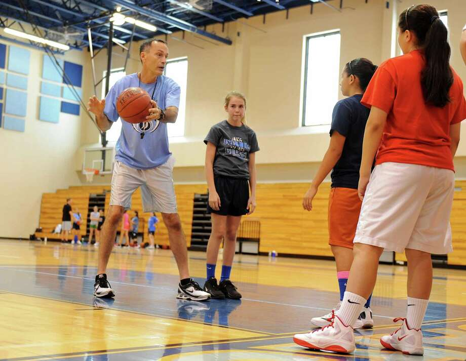 Johnson head girls basketball coach Randy Evans instructs a group of campers during the Johnson basketball summer camp for girls going into the sixth through ninth grades. Area high schools are running summer camps for a variety of sports, teaching fundamentals to different age groups. Photo: John Albright / For North Central News / John Albright / www.johnalbrightphoto.com