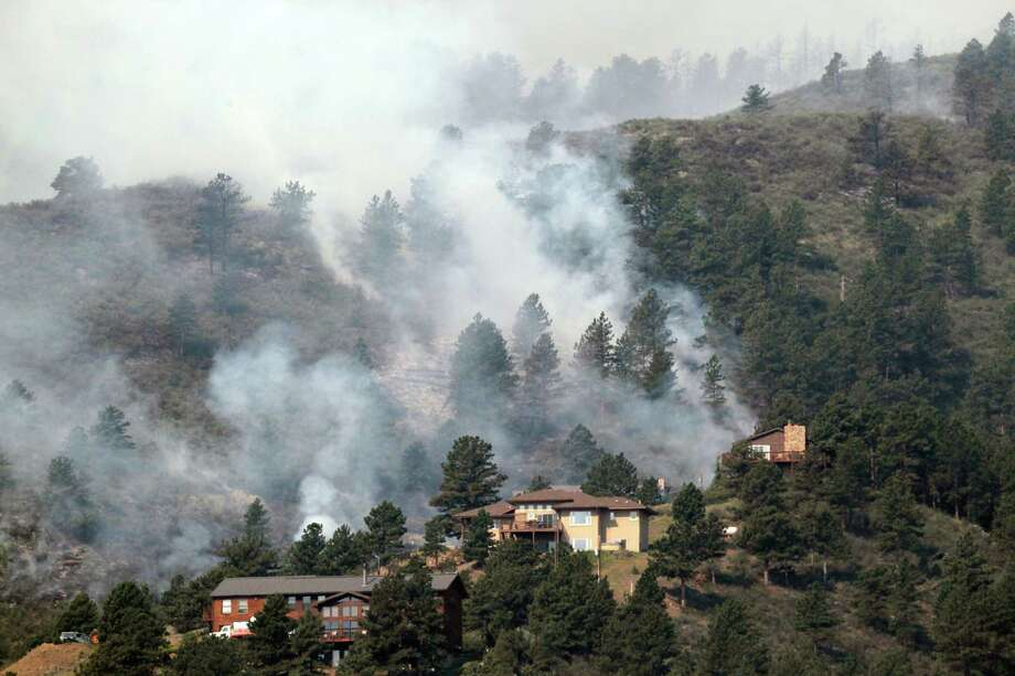 Fire burns in trees behind homes on the High Park wildfire near Fort Collins, Colo., on Monday, June 11, 2012. The wildfire is burning out of control in northern Colorado, while an unchecked blaze choked a small community in southern New Mexico as authorities in both regions battled fires Monday. (AP Photo/Ed Andrieski) Photo: Ed Andrieski / AP