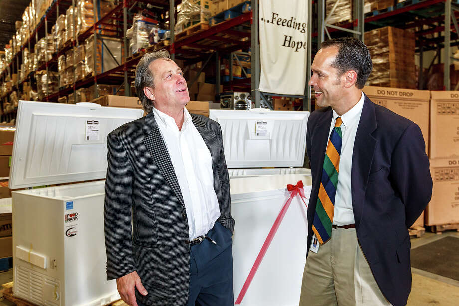 Kim Adler, President of 1st Source Servall (left) and Eric Cooper, President and CEO of the San Antonio Food Bank, visit at the Food Bank on May 15, 2012.  Adler's company, one of North America's largest distributors of applicance parts with operations and a regional distribution center in San Antonio, donated 27 large food storage freezers to 21 local orgainizations that provide services and food assistance programs to some of the most vulnerable populations in the community.  Photo by Marvin Pfeiffer / Prime Time Newspapers Photo: MARVIN PFEIFFER, Marvin Pfeiffer / Prime Time Newspapers / Prime Time Newspapers 2012
