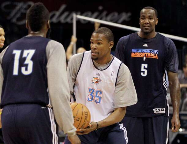 Oklahoma City Thunder small forward Kevin Durant (35) takes the bakll between James Harden (13) and Kendrick Perkins (5) during practice, Monday, June 11, 2012, in Oklahoma City. Game 1 of  NBA finals basketball between the Miami Heat and Thunder is Tuesday. (AP Photo/Jeff Roberson) Photo: Jeff Roberson, STF / AP