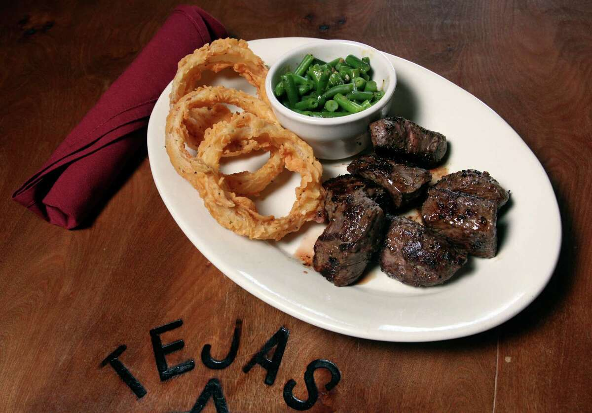 Meats at Tejas Steakhouse & Saloon, including the KC steak served with onion rings and green beans, are cooked over an open flame.