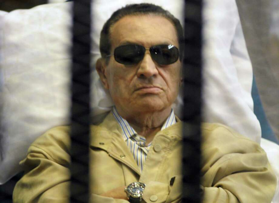 FILE - In this Saturday, June 2, 2012 file photo, Egypt's ex-President Hosni Mubarak lays on a gurney inside a barred cage in the police academy courthouse in Cairo, Egypt. Doctors used a defibrillator twice on Hosni Mubarak when they could not find a pulse Monday, the latest health crisis for the ousted Egyptian president since he was sentenced to life and moved to a prison hospital nine days ago, security officials said. In his last public appearance at his June 2 sentencing, the bedridden Mubarak sat stone-faced in the defendants' cage in the courtroom, his eyes hidden behind dark glasses. Officials said he broke into tears when he learned he was being transferred to a prison. Photo: AP