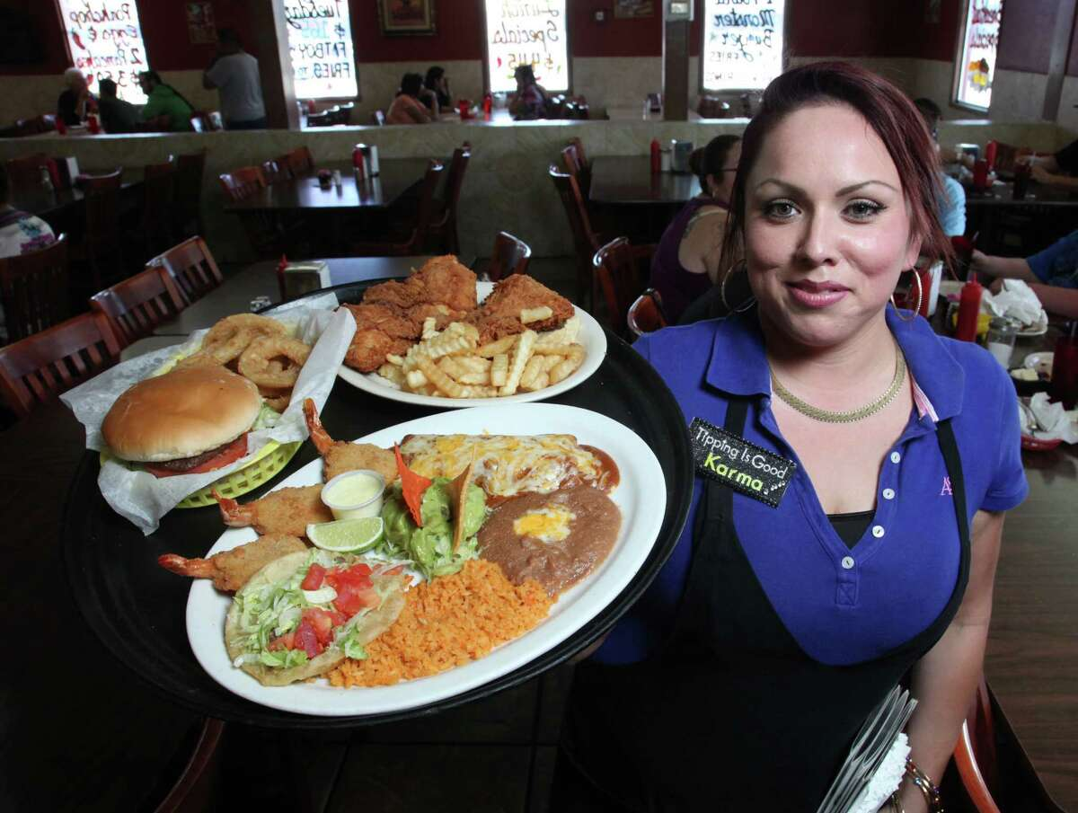 Malt House waitress Nina Ramirez carries a tray of food to customers.
