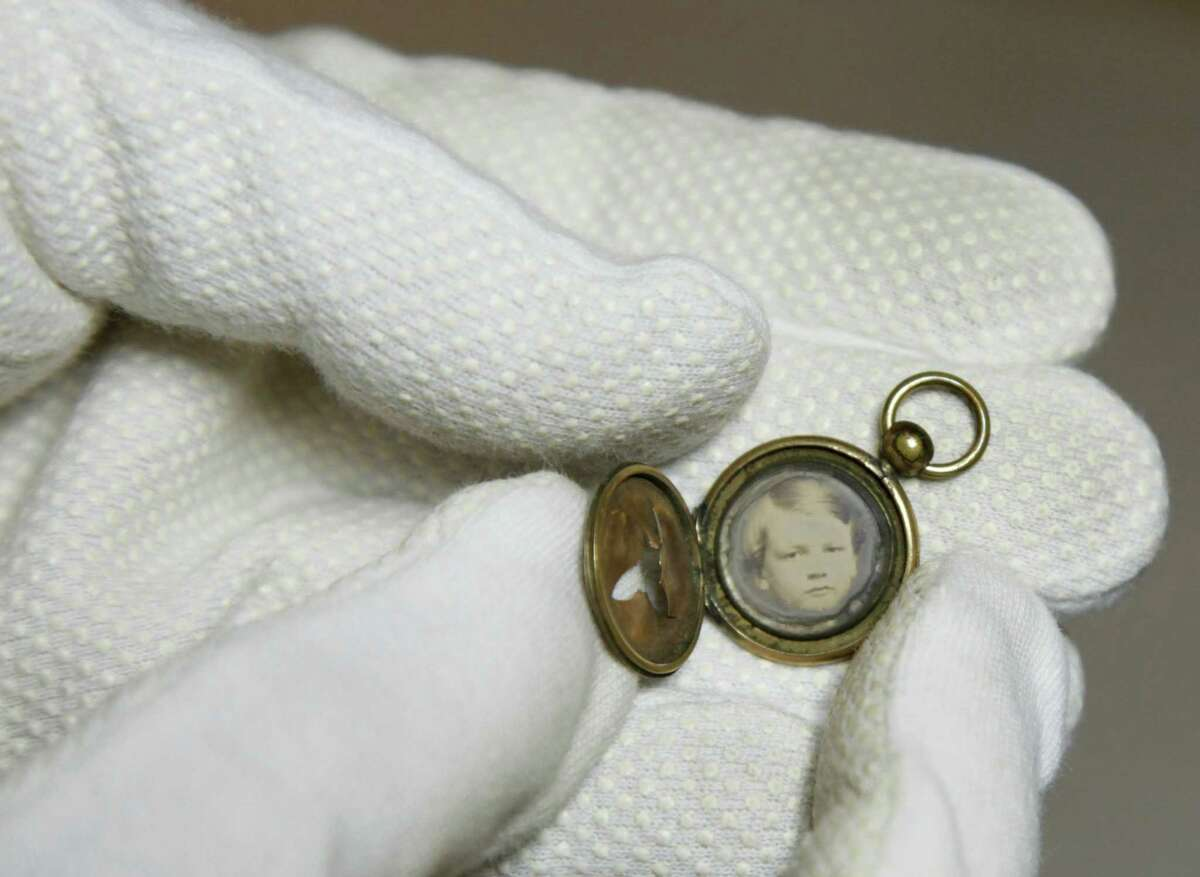 Ann Drury Wellford, manager of Photographic Services for The Museum of the Confederacy, holds a Civil War battlefield photo at the museum in Richmond, Va., Friday, May 25, 2012. This Gem daguerreotype locket was found by a soldier in Hampton's cavalry brigade on a battlefield in 1863. The Museum of the Confederacy is publicly releasing eight images recovered on battlefields of unidentified persons in the admittedly remote chance a descendant might recognize a facial resemblance or make a connection the battlefields where they were found.
