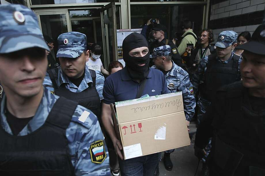 An investigator guarded by Russian police officers carries a box after a police search in Russian opposition leader Alexei Navalny flat in Moscow, Russia, June 11, 2012. Russian investigators searched the apartments of several protest leaders Monday and called them in for questioning Tuesday, making it difficult if not impossible for them to lead a mass demonstration against President Vladimir Putin planned for the June 12 national holiday. (AP Photo/Leonid Lebedev) Photo: Leonid Lebedev, Associated Press