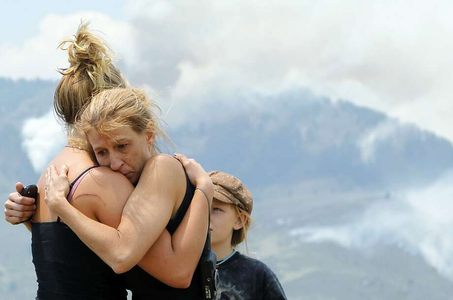 Tracy Greenwood embraces her daughter Mariah Greenwood, left, as they watch the High Park wildfire burn around their home west of Fort Collins, Colo., on Monday, June 11, 2012. (AP Photo/Ed Andrieski) Photo: Ed Andrieski, Associated Press