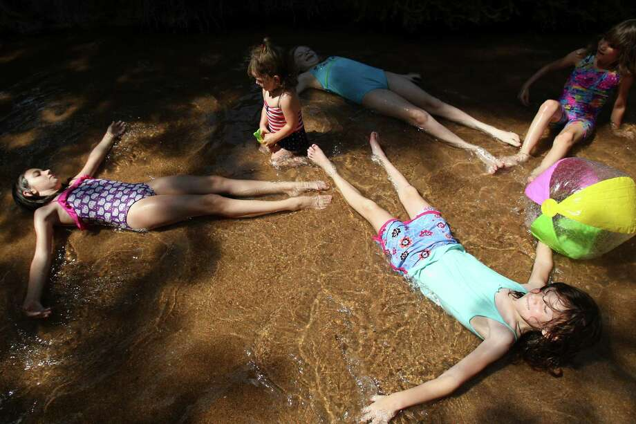 (Bottom right corner) Zoee Tetlow, 8, (left) Star Clinton, 10, (center) Athena Vasquez, 1, and Kendra Swartz, 9, (top right corner) Bell Tetlow,6, cool off in the Riverbank Monday June 11, 2012 at the San Antonio Zoo. Adults and kids are welcome to cool off in the water while visiting the zoo. Photo: Julysa Sosa, San Antonio Express-News / © 2012 San Antonio Express-News