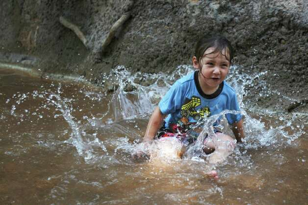 Conner Vasquez, 3, splashes in the Riverbank Monday June 11, 2012 at the San Antonio Zoo. Adults and kids are welcome to cool off in the water while visiting the zoo. Photo: Julysa Sosa, San Antonio Express-News / © 2012 San Antonio Express-News