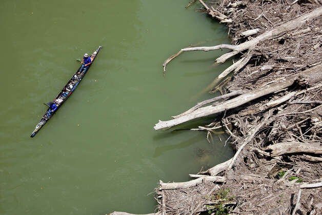 House of Blues team members Lauren DeLouche, front, and Michael Simmons navigate a logjam by the Thomaston River Road bridge over the Guadalupe River south of Cuero, Texas during the 2012 Texas Water Safari canoe race, Monday, June 11, 2012. The race started in San Marcos on Saturday and ends at Seadrift, Texas by San Antonio Bay. The House of Blues started as a three-member team but by the bridge they were down to two. The third member Jeanette Burris became ill and was taken to an area hospital by her daughter, according to a family team member. She was checked and released later. Competitors have until Wednesday to complete the 260-mile course. Photo: Jerry Lara, San Antonio Express-News / © 2012 San Antonio Express-News