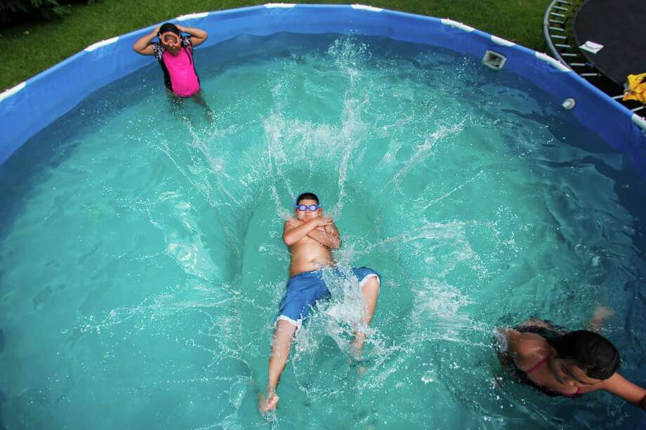 Kids play in a pool, Monday, June 11, 2012, in Rosenberg. Photo: Michael Paulsen, Houston Chronicle / © 2012 Houston Chronicle