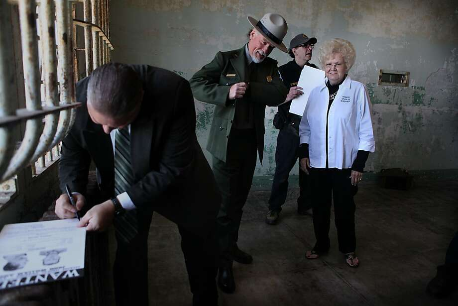 U.S. Marshal Michael Dyke  signs a poster while Mearl Anglin Taylor (right), sister of two escapees, visits with a ranger. Photo: Liz Hafalia, The Chronicle