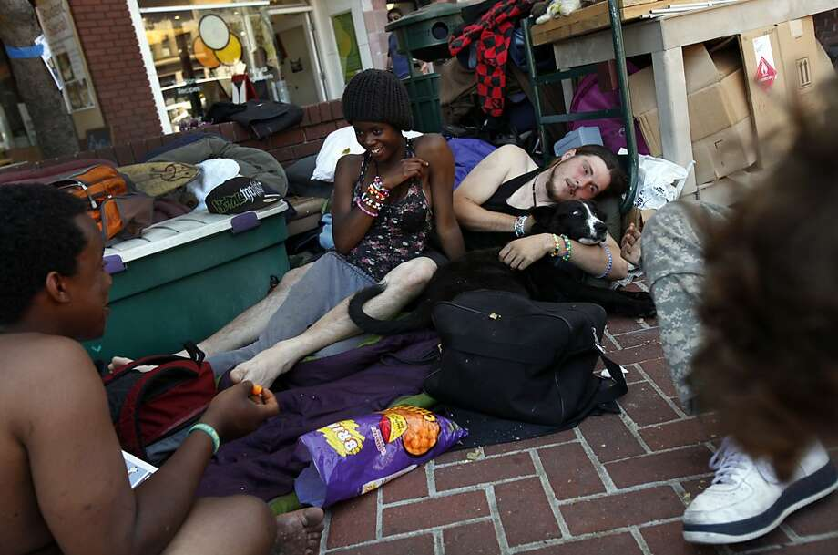 A young woman and man pass time at their campsite in the plaza at Shattuck Avenue and Center Street in Berkeley. Photo: Sarah Rice, Special To The Chronicle