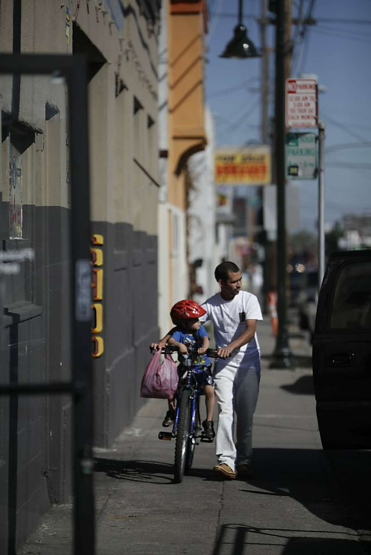 A father holds his son on a bicycle as they walk on Foothill Boulevard between Harrington Avenue and 38th Avenue on Monday, June 11, 2012 in San Francisco, Calif.