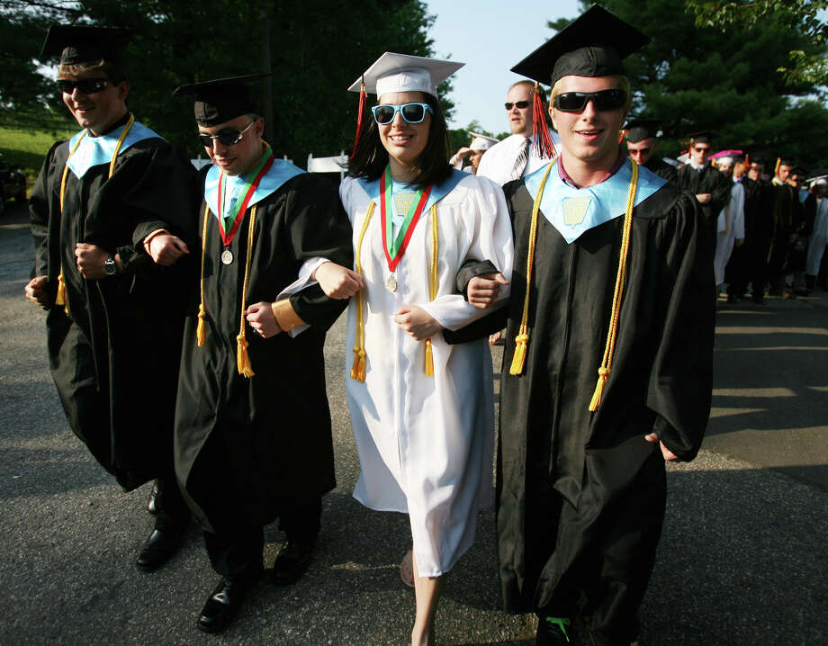 From left; Senior class officers Billy Maloney, Stephen Arena, Valerie Emini, and Edward Hunt, walk arm in arm as they lead their classmates into the Shelton High School Graduation on Monday, June 11, 2012. Photo: Brian A. Pounds / Connecticut Post