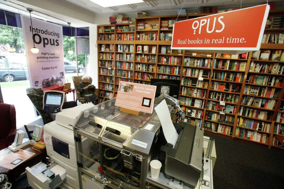 In this June 5, 2012, photo, a customer reads a book by the Espresso Book Machine, known as Opus, at Politics and Prose bookstore in Washington.  Photo: Jacquelyn Martin