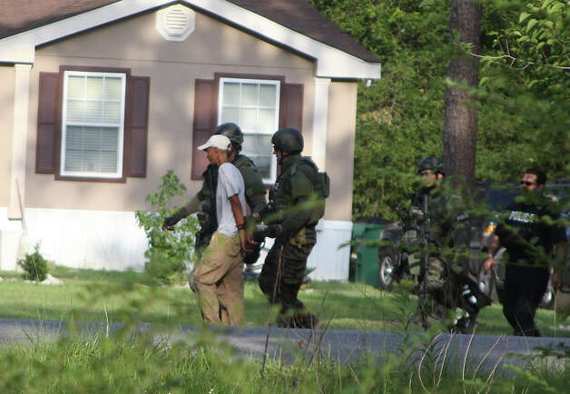 SWAT Team members escort a female suspect who allegedly shot a female relative at a home at 1330 Villa Road in Kountze on Monday, June 11 and then held officers at bay with a loaded shotgun. The standoff lasted for over six hours before the woman was taken into custody. Photo: David Lisenby