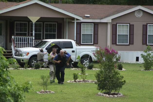 Deputy Donnie Gulley provides cover for Sheriff Ed Cain during a standoff at a home at 1330 Villa Road in Kountze on Monday, June 11 after a woman shot her relative and then held officers at bay with a loaded shotgun. The standoff lasted for over six hours before the woman was taken into custody. Photo: David Lisenby