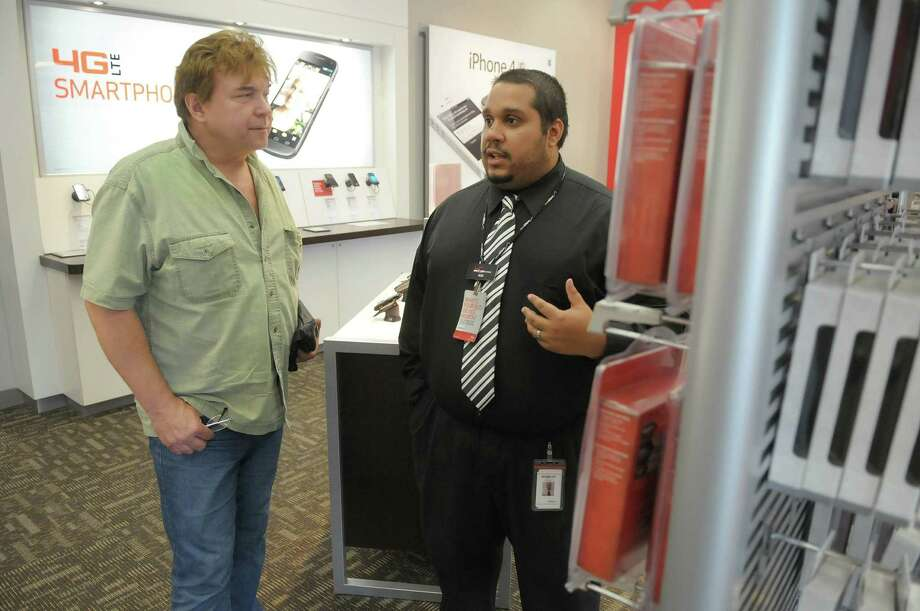 Danny Marcil, left, of Colonie talks to Verizon salesman Rob Turner  at the Verizon Wireless store on Central Avenue on Monday, June 11, 2012 in Colonie, NY.  Marcil came in to look at switching his cellular provider to Verizon and he was checking out the different plans.    Verizon Wireless was named number one in the Albany area for cell phone service in a new study released Monday.  (Paul Buckowski / Times Union) Photo: Paul Buckowski / 00018046A