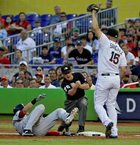 First-base umpire D.J. Reyburn makes the call as Miami's Gaby Sanchez tags out Boston's Ryan Sweeney on a pickoff in the second inning Monday. Photo: Joe Rimkus Jr. / Miami Herald