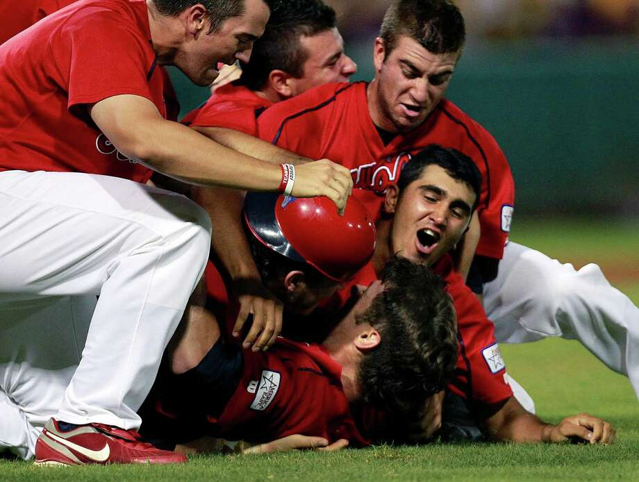 Stony Brook players mob Frankie Vanderka, bottom, after he completed a three-hitter against LSU. Photo: Gerald Herbert / AP