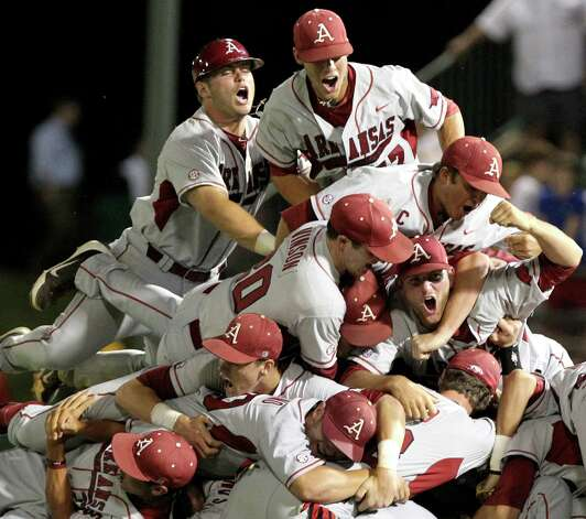Arkansas players pile on top of each other after defeating Baylor in the 10th inning of an NCAA college baseball tournament super regional game, Monday, June 11, 2012, in Waco. Arkansas advances to the College World Series. Photo: AP Photo/Waco Tribune Herald, Jerry Larson
