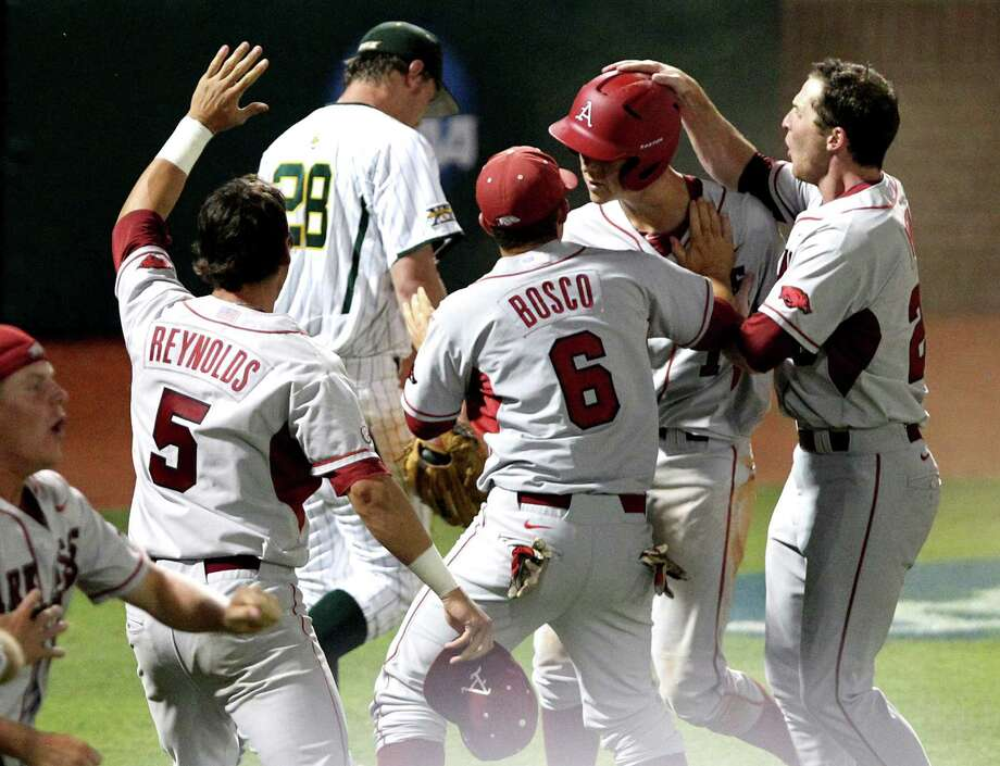 Arkansas players grab Brian Anderson, second from right, after scoring against Baylor in the 10th inning of their NCAA college baseball tournament super regional game, Monday, June 11, 2012, in Waco. Arkansas advances to the College World Series with the 1-0 victory. Photo: AP Photo/Waco Tribune Herald, Jerry Larson
