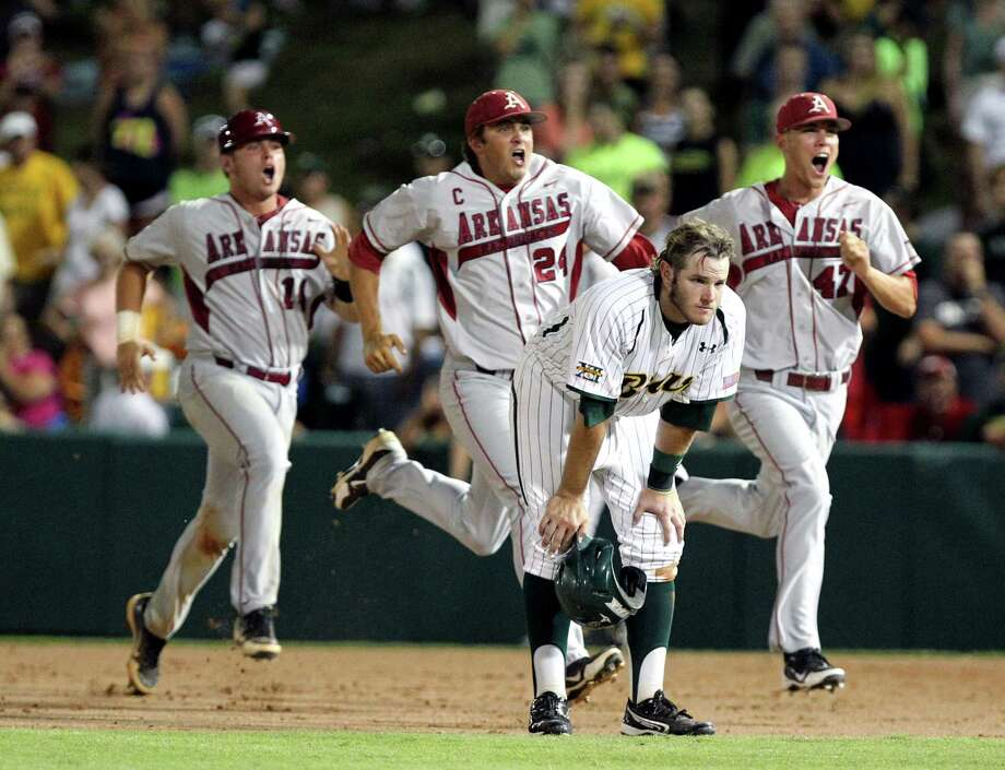 Arkansas players John Clay Reeves, left, DJ Baxendale (24), and Tyler Wright, right run past Baylor's Max Muncy (9) after defeating Baylor in the 10th inning of an NCAA college baseball tournament super regional game, Monday,  June 11, 2012, in Waco. Arkansas advances to the College World Series. Photo: AP Photo/Waco Tribune Herald, Jerry Larson