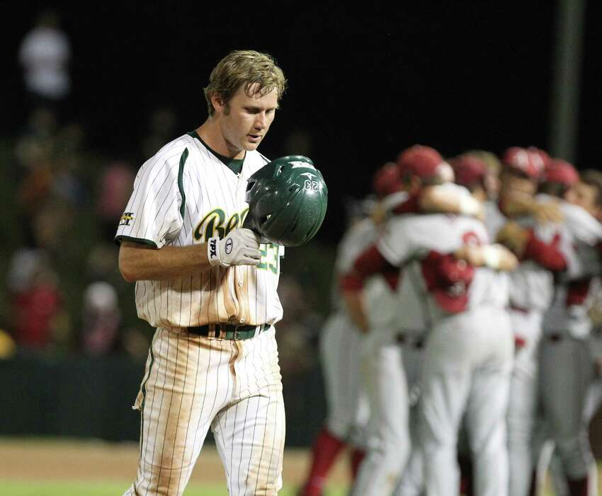 Arkansas players celebrate while Baylor baserunner Dan Evatt (23) walks back to the during after their NCAA college baseball tournament super regional game, Monday, June 11, 2012, in Waco. Arkansas advancesto the College World Series with the 1-0 victory.