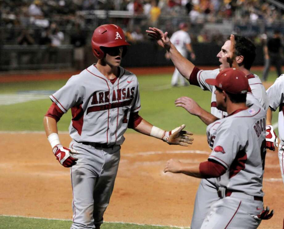 Arkansas' Brian Anderson, left, celebrates with teammates after scoring against Baylor in the 10th inning of an NCAA college baseball tournament super regional game, Monday,  June 11, 2012, in Waco. Photo: AP Photo/Waco Tribune Herald, Rod Aydelotte