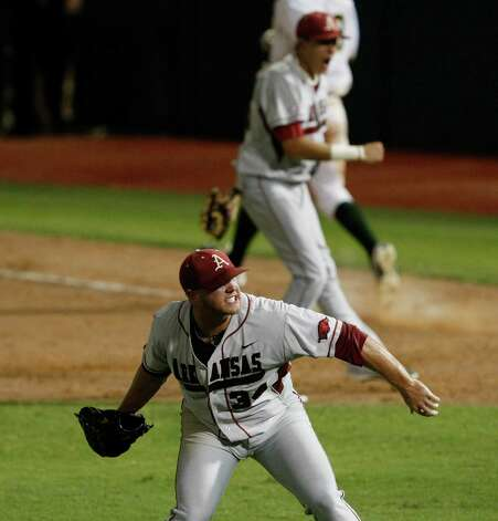 Arkansas relief pitcher Colby Suggs (34) throw up his glove after defeating Baylor 1-0 during an NCAA college baseball tournament super regional game, Monday,  June 11, 2012, in Waco. Arkansas advances to the College World Series. Photo: AP Photo/Waco Tribune Herald, Jose Yau