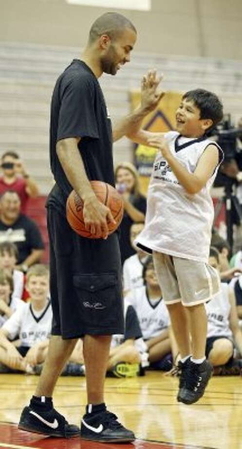 Spurs' Tony Parker (left) high-fives Andrew Trevino, 8, during the Spurs Basketball Camp held at the University of the Incarnate Word Monday, June 11, 2012. (Edward A. Ornelas / San Antonio Express-News)