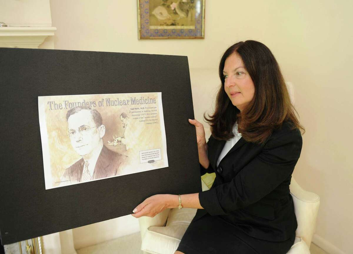 Barbara Hertz looks at a poster of her father Saul Hertz in her Greenwich home Monday, June 11, 2012. Greenwich resident Barbara Hertz's father died when she was 3, but she eventually learned that he had discovered the use of radioactive iodine as a treatment for thyroid cancer.
