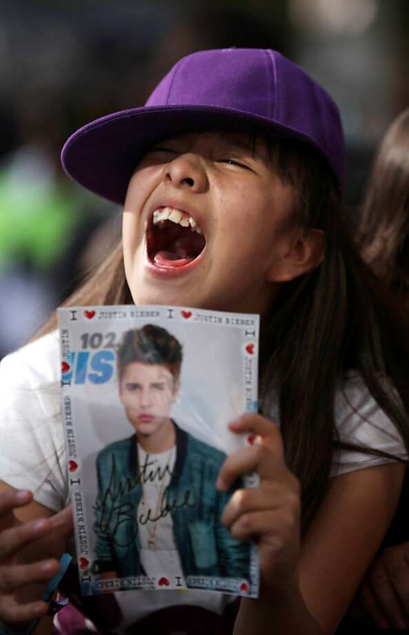 A fan of pop star Justin Bieber cheers outside a hotel where Bieber gave a news conference in Mexico City, Monday, June 11, 2012. Bieber will perform in a free open-air concert tonight at the Mexico City's main historic plaza, the Zocalo. (AP Photo/Alexandre Meneghini) Photo: Alexandre Meneghini, Associated Press