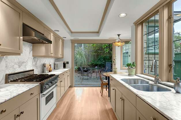 Kitchen of 2316 Nob Hill Ave. N. The 2,400-square-foot house, built in 1914, has four bedrooms, 1.75 bathrooms, ribboned oak floors, box beam ceilings, built-in cabinets with leaded glass, wainscoting, a front porch, a back patio and a Chinese granite water feature on a 3,840-square-foot lot. It's listed for $824,900. Photo: Courtesy Ron Waxman And Ricklie Stone/Coldwell Banker Bain