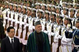 Chinese President Hu Jintao, front left, and Afghan President Hamid Karzai, front right, review an honor guard during a welcoming ceremony at the Great Hall of the People in Beijing Friday, June 8, 2012. (AP Photo/Alexander F. Yuan)
