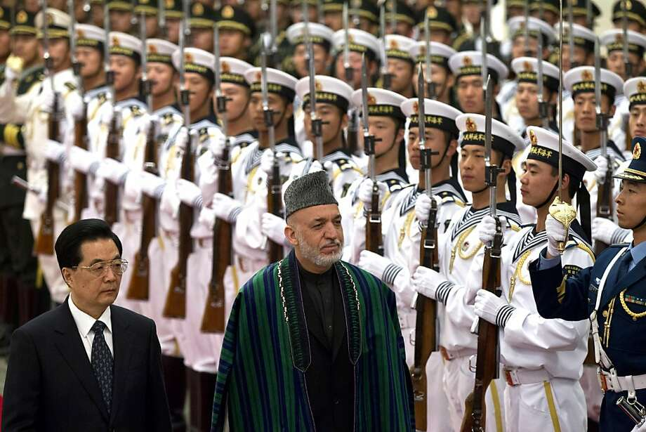 Chinese President Hu Jintao, front left, and Afghan President Hamid Karzai, front right, review an honor guard during a welcoming ceremony at the Great Hall of the People in Beijing Friday, June 8, 2012. (AP Photo/Alexander F. Yuan) Photo: Alexander F. Yuan, Associated Press