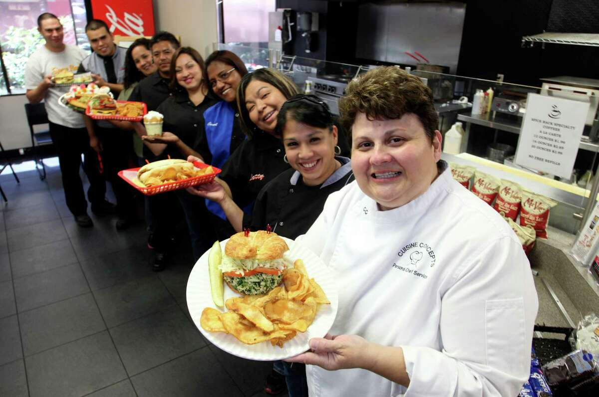 Connie Santos, owner of Spice Rack Deli, is holding a Fiesta Burger with her staff behind her.