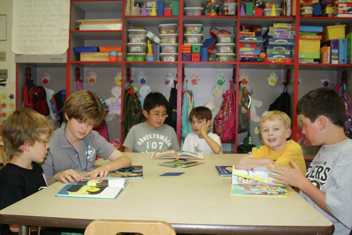 Every Wednesday afternoon at Holmes School, Mr. Bulkley's fifth grade class visits Miss Novotnik's kindergarten class to read with them. The reading buddies program started five years ago. It fosters responsibility and mentoring skills in fifth-graders, and the kindergarteners enjoy having older reading role models. From left, Cooper Zalinsky, Nick Giotis, Jacob Won, Morgan Brown, Liam Tomaszewski and Johan Trippitelli read books. Darien, Conn.