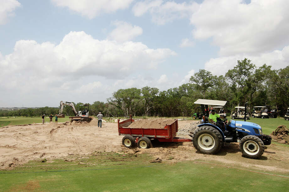Workers remove sand from the 12th green at the TPC San Antonio Oaks course, Tuesday, June 12, 2012. Major renovations are underway in responds to player's complaints. Photo: Jerry Lara, San Antonio Express-News / © 2012 San Antonio Express-News
