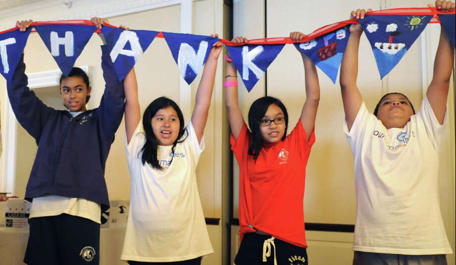 Students from Rogers International School hold up a thank you banner during the graduation ceremony and picnic for the Young Mariners Foundation after-school program at the Stamford Yacht Club on Tuesday, June 12, 2012. Photo: Lindsay Niegelberg / Stamford Advocate