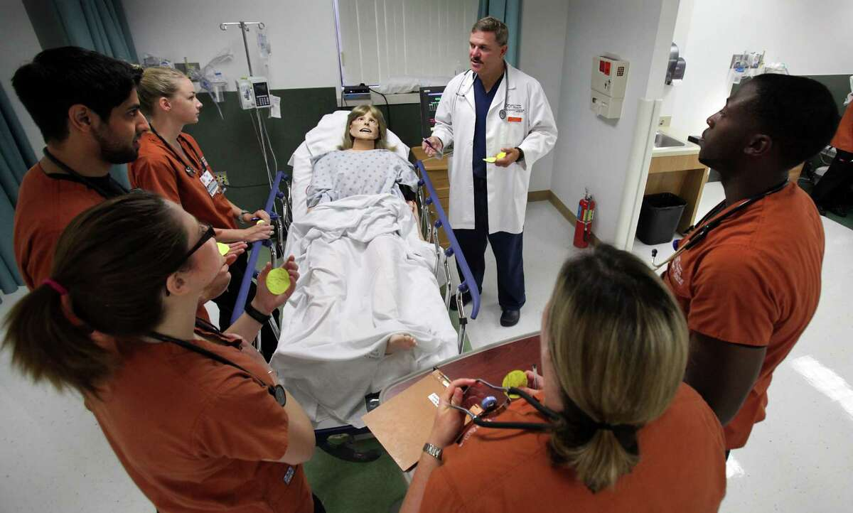 """James Cleveland, an assistant professor of nursing, debriefs students after running through a learning scenario with a programmable mannequin. """"I've had students cry when a (simulated) patient dies,"""" he says."""