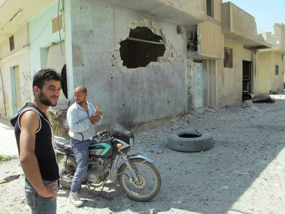 Residents of Homs stand next to a hole in a building damaged after shelling on Monday in the Talbisah area of the city. Photo: DAVID MANYUA / AFP